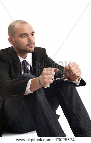 Close-up of handcuffed businessman over white background