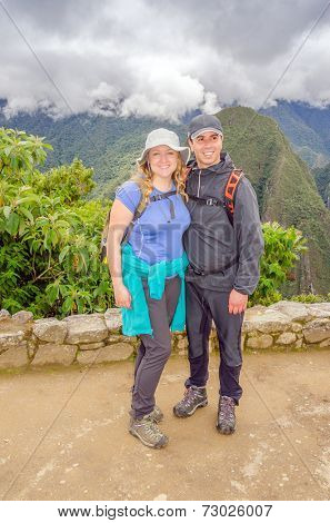 Machu Picchu, Peru - inter-ethnic couple of tourists posing for photo