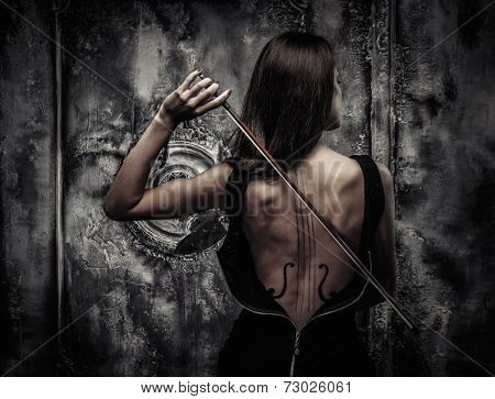 Woman in dress with violin body art holding bow