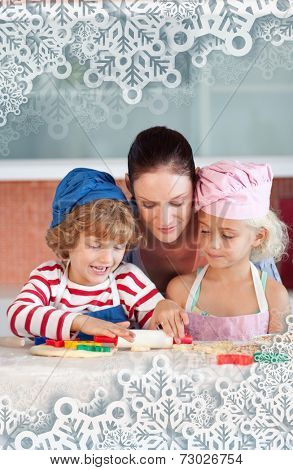 Joyful mother baking with her children against snowflakes on silver