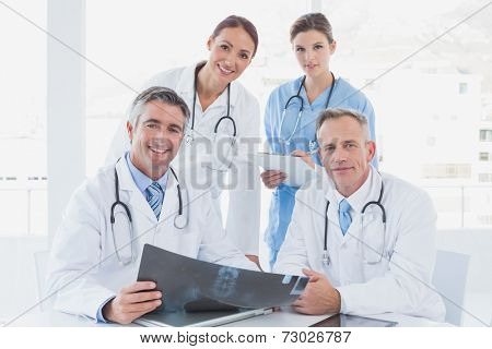 Doctor holding up an x-ray with fellow doctors