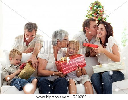 Composite image of Family giving presents for Christmas with snow falling