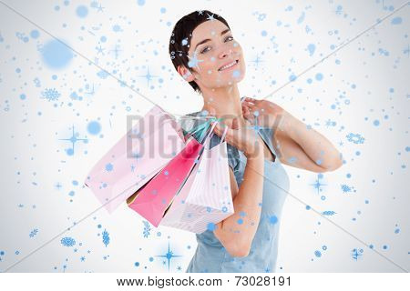Darkhaired woman posing with shopping bags against snow falling