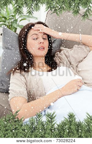 Sick woman lying on the sofa and touching her forehead against snow falling
