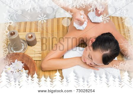 Peaceful brunette enjoying a herbal compress massage against fir tree forest and snowflakes