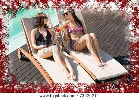 Women holding drinks by swimming pool against snow