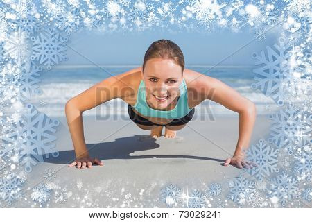 Composite image of fit woman in plank position on the beach against snow