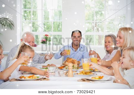 Composite image of Family toasting at thanksgiving against snow falling