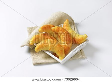 overhead view of five buttery croissants served on the wooden tray