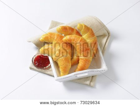 wooden tray with french buttery croissants and bowl of strawberry marmalade