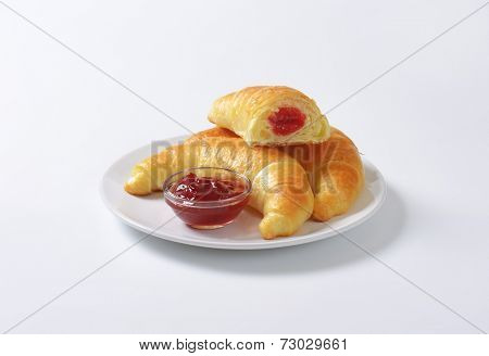 french buttery croissants with strawberry marmalade, served on the plate