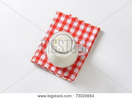 overhead view of glass pitcher with liter of cow's milk
