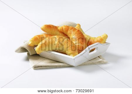 five french buttery croissants on the wooden tray with fabric linen