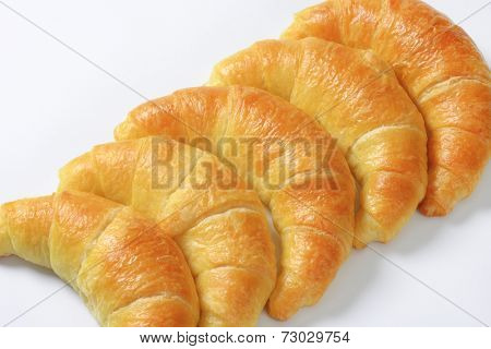 detail of five lined buttery croissants