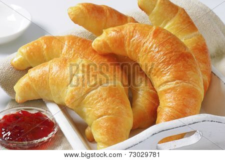 detail of french buttery croissants with bowl of strawberry jam served on the wooden tray