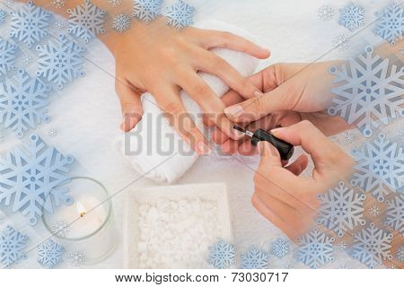 Nail technician painting customers nails against snowflake frame