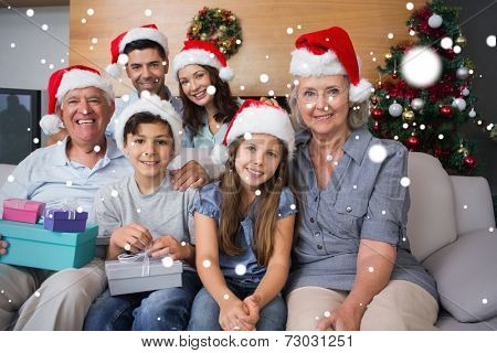 Extended family in Christmas hats with gift boxes in living room against snow