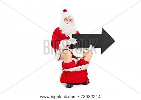 Santa Claus holding a big black arrow seated on a toilet isolated on white background