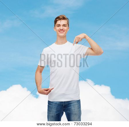 gesture, advertising, dream and people concept - smiling young man in blank white t-shirt pointing fingers on himself over blue sky background