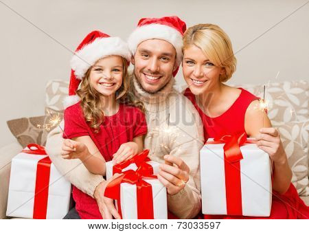 family, christmas, x-mas, winter, happiness and people concept - smiling family in santa helper hats with many gift boxes and bengal lights