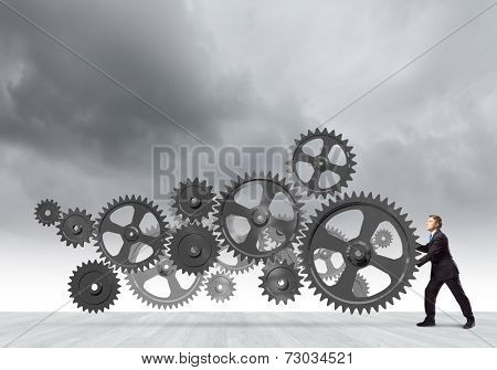 Young determined businessman making gear mechanism move
