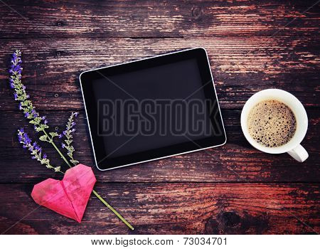 electronic tablet device on a wooden workspace table with coffee and flower toned with a retro vintage instagram filter effect