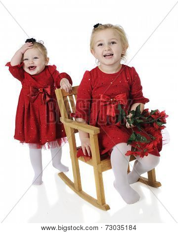A preschooler and her baby sister all dressed up for Christmas.  Both are laughing in their identical red dresses.  On a white background.