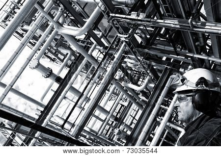 oil worker in profile with large pipelines construction, analog processing effect