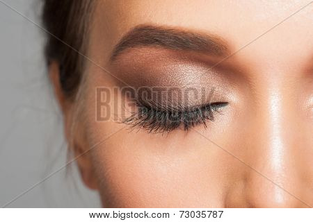 Closeup image of closed woman eye with beautiful bright makeup, smoky eyes