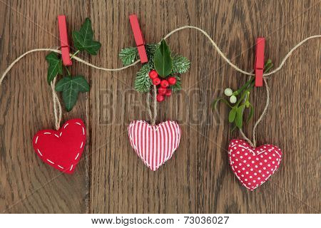 Christmas heart decoration with holly, ivy, mistletoe and fir hanging on a string line over oak background.