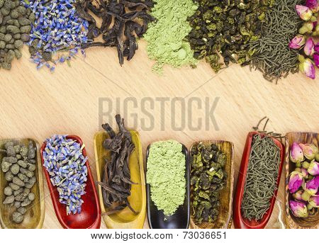 border frame of different dry tea addition  in scoops on wooden table background, top view