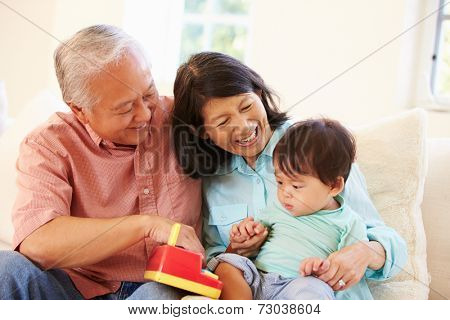 Grandparents And Grandson Playing With Toy Together
