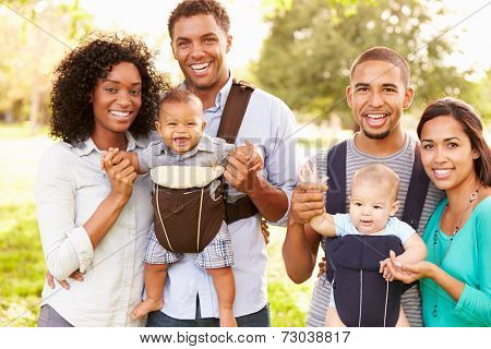 Portrait Of Two Families With Baby Carriers In Park