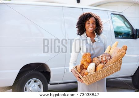 Female Baker Delivering Bread Standing In Front Of Van