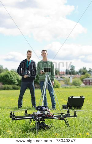 Young technicians holding remote controls with UAV helicopter in foreground at park