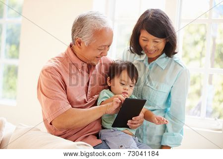 Grandparents And Grandson Using Digital Tablet Together
