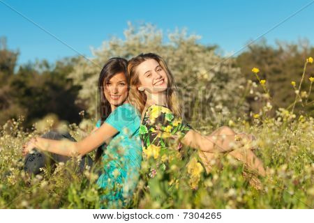 Two Beautiful Young Women Sitting In Blooming Meadow