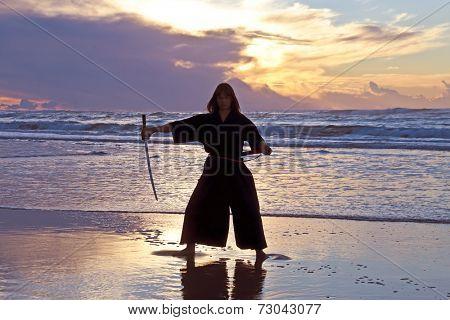 Young samurai women with Japanese sword(Katana) at sunset on the beach