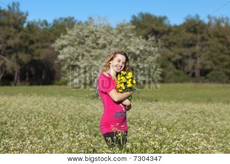 Beautiful Young Woman Standing In Blooming Meadow