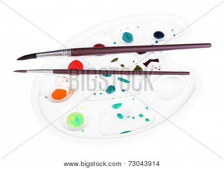 Multicoloured paint and brushes on palette isolated on white