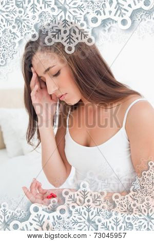 Woman looking worried as she decides whether or not to take the tablets against snowflakes on silver