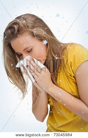 Close up of a blond young woman blowing against snow falling