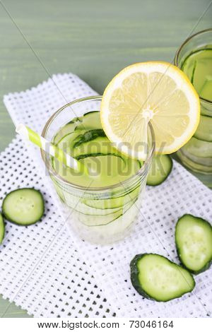 Glass of cucumber cocktail on napkin on wooden background