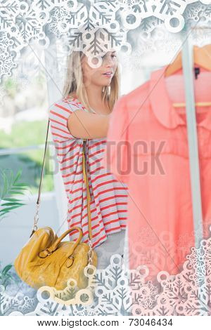 Woman standing and looking at clothes against snowflakes on silver