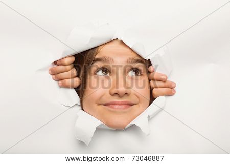 Cute little girl peeking through paper on white background