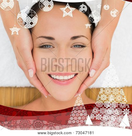 Peaceful brunette enjoying a facial massage against christmas themed frame