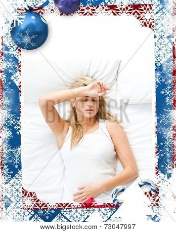 Upset woman having a migraine lying on a bed at home against christmas themed frame