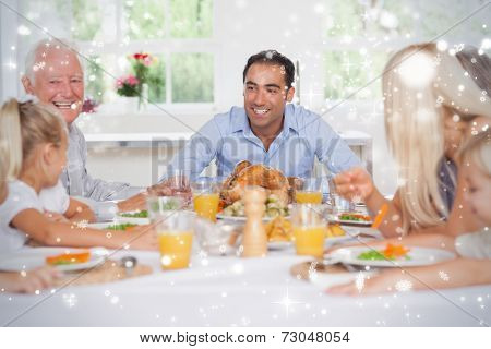 Composite image of Happy family at thanksgiving against snow falling