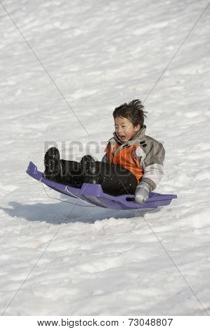 Boy catching air on sled