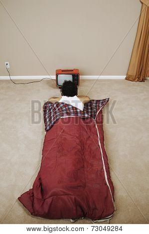 Young man in a sleeping bag watching TV